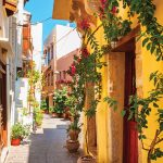 Flowered vines adorn quaint buildings along a cozy street in Chania, Greece.