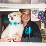 Smiling Seattle Barkery Employee holding a white fluffy dog and peering out of a window