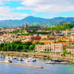Cityscape of Messina, Sicily, Italy. Multi colored image with buildings, cathedral, mountains, blue sky with clouds, boats and yachts in the harbor or cruise port of Messina.