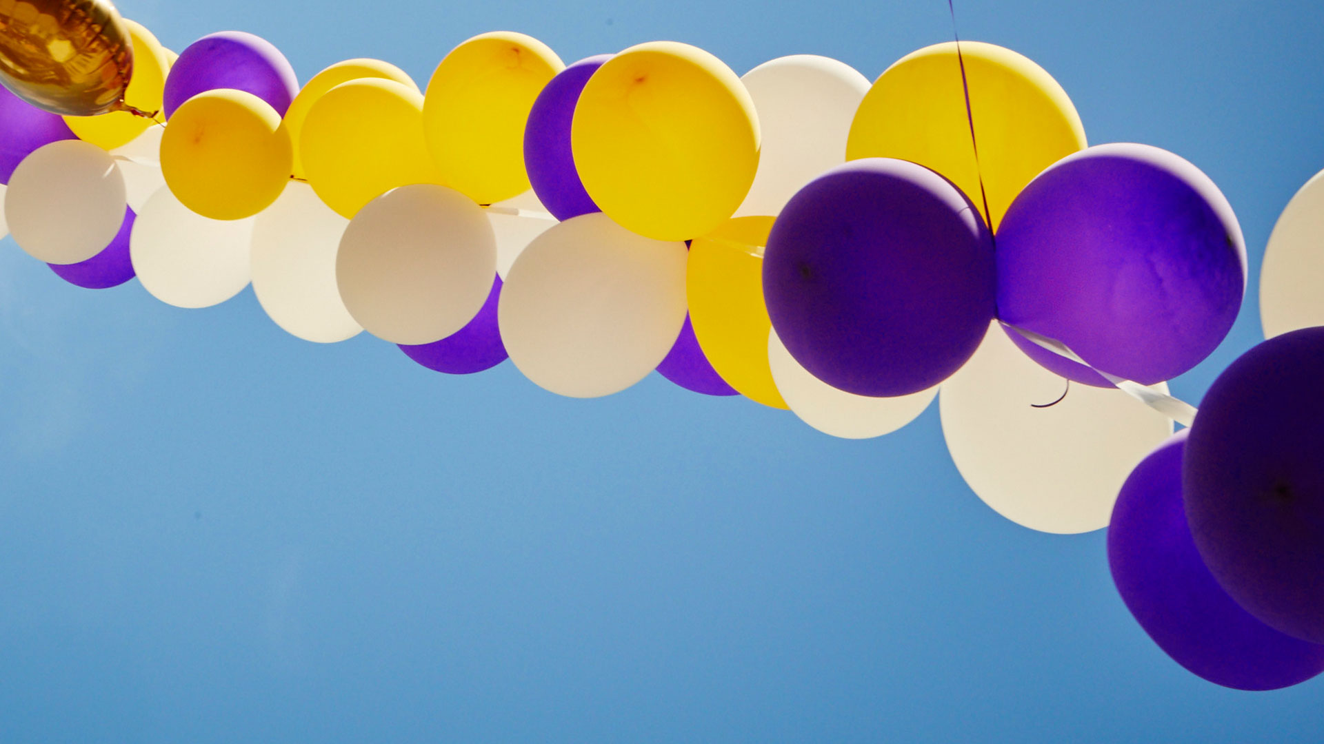 Purple, gold and white balloons against a blue sky