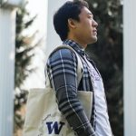 Man with W Totee tote bag over his shoulder, in front of the UW Columns