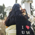 Girl with I (heart) UW Totee tote bag over her shoulder, in front of the UW Columns