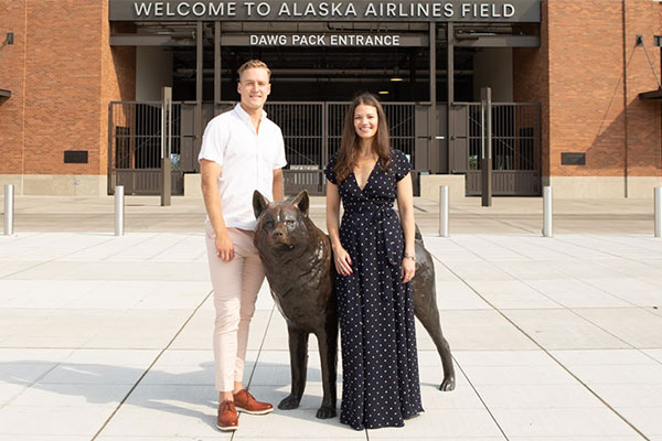 Allison Claire founder and UW football player Race Porter in front of Husky Stadium