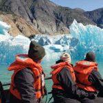 Alaskan iceberg with hills in the background and people in a boat in the foreground