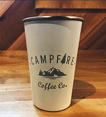 Photo of a piping hot cup of Campfire Coffee in a logo-emblazoned to-go cup