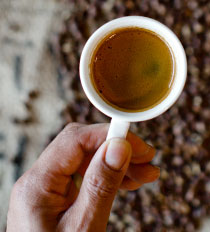 Photo of a hand holding a cup of Boon Boona coffee with soft-focus coffee beans in the background