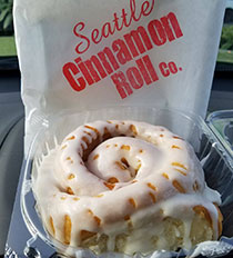 Photo of a cinnamon roll with drippy white glaze