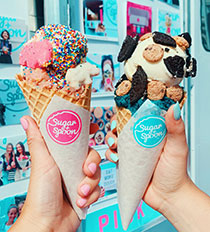 """Photo of hands holding scoops of edible cookie dough in ice cream cones emblazoned with """"Sugar + Spoon"""" logos"""
