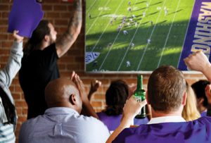 Fans cheer together while watching a football game at a restaurant