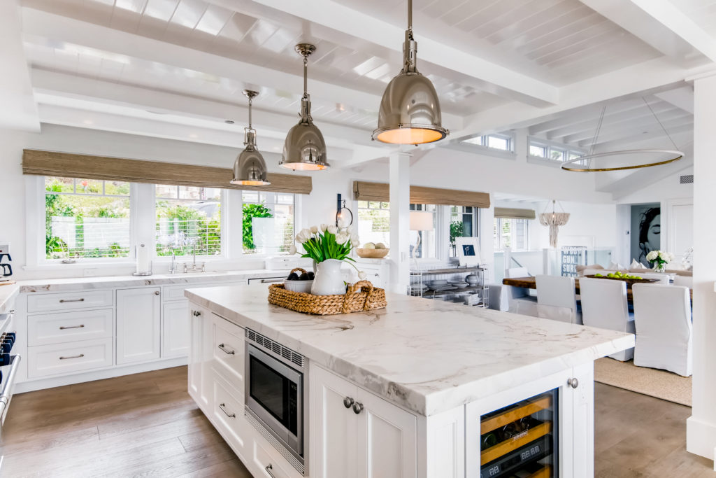 real estate photo of beautiful kitchen with metal pendant lights, kitchen island, white paneling on ceilings - from Virtuance - real estate marketing help
