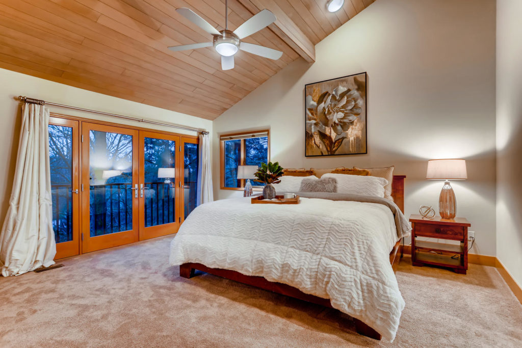 real estate image of master bedroom with wood paneled ceilings