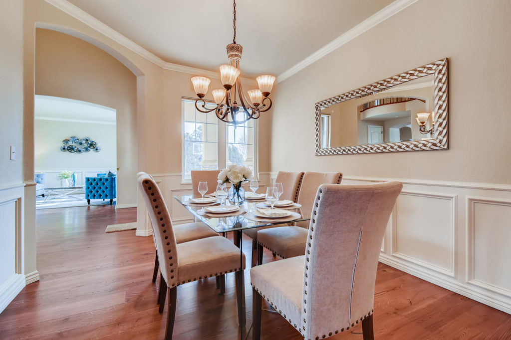 Real estate picture of a dining room with pastel chairs