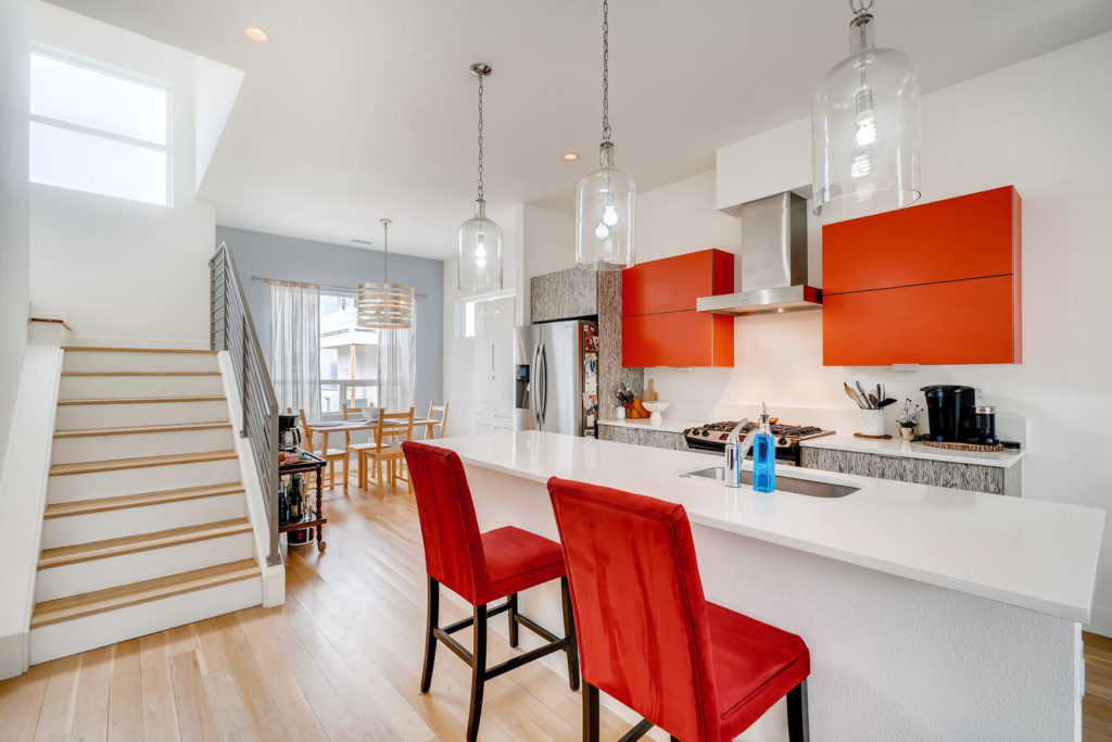 Real estate image of the kitchen with red chairs and cabinets