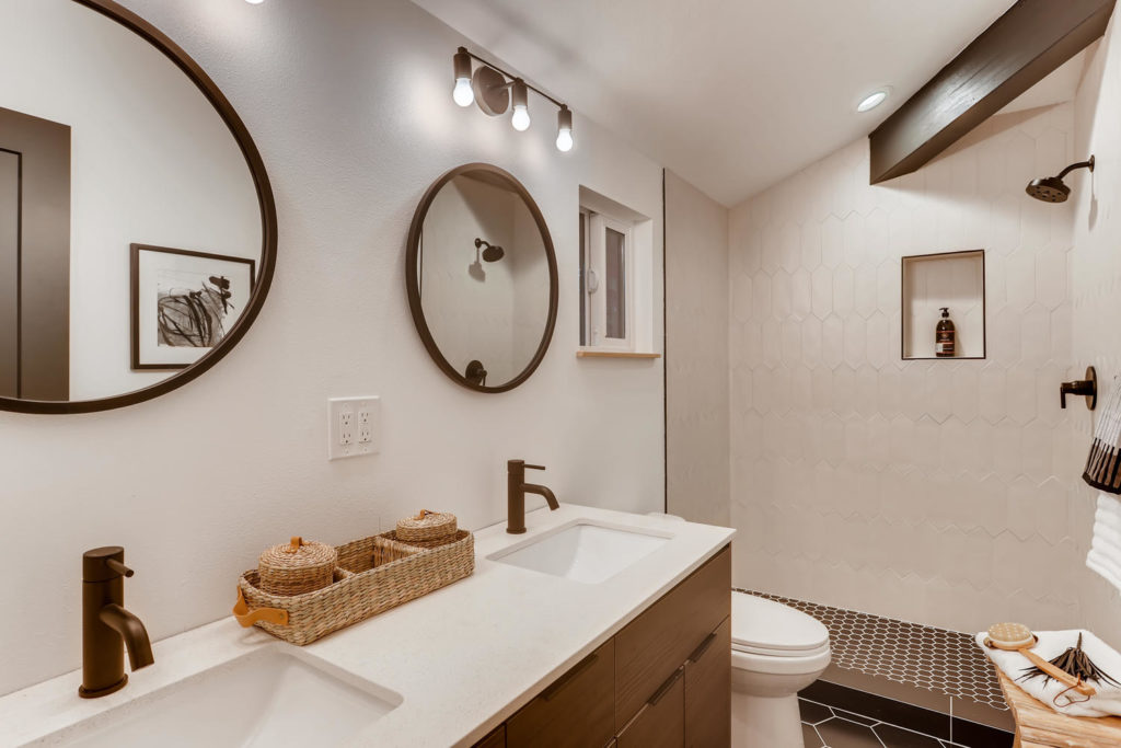 Real estate picture of the bathroom with round mirrors
