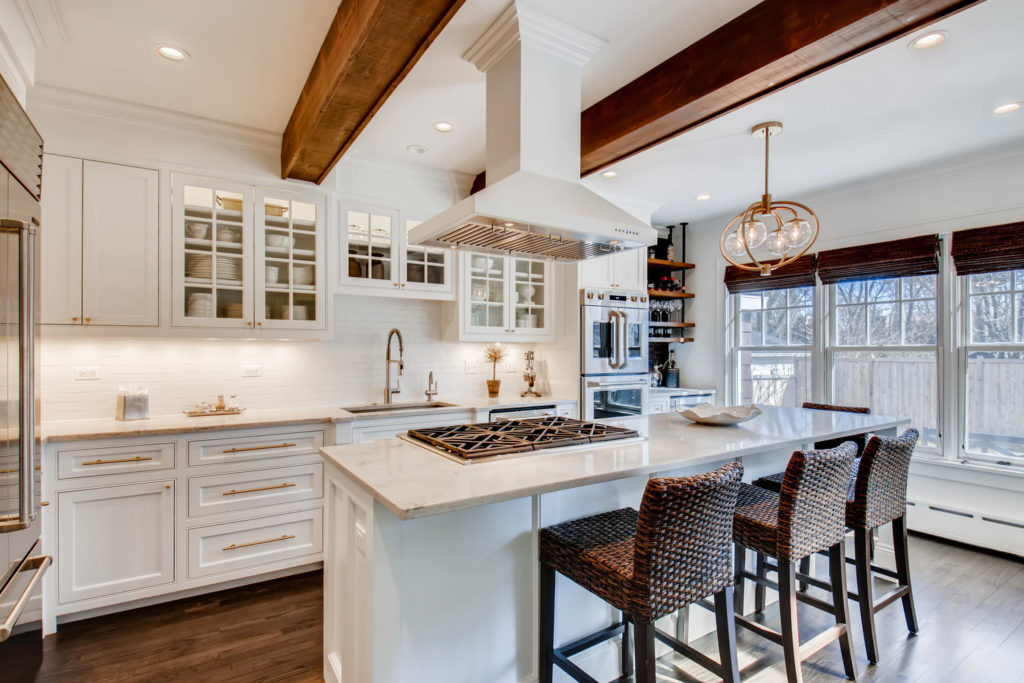 Kitchen with white cabinets and counters, beams