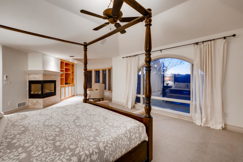 Bedroom with canopy bed frame and fireplace