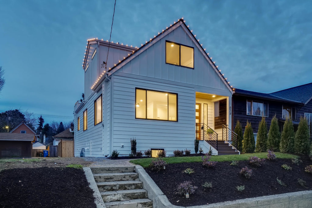 White home at twilight with string lights on roof