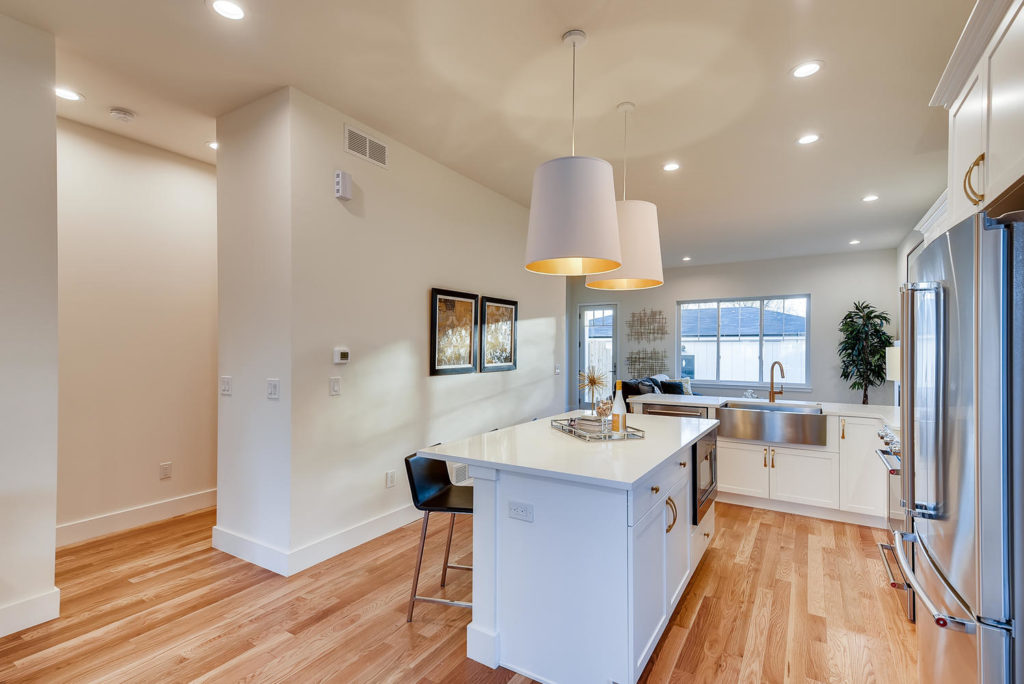 Kitchen with white island and large white pendant lights