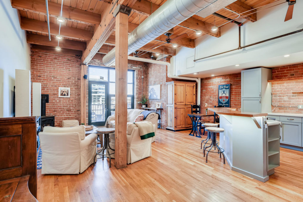 Living room loft with brick wall and exposed beams