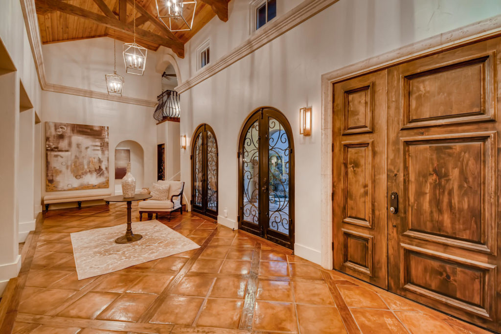 Foyer with clay tile floors and wood beams