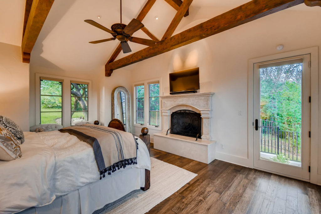 Master bedroom with fireplace and wood beams
