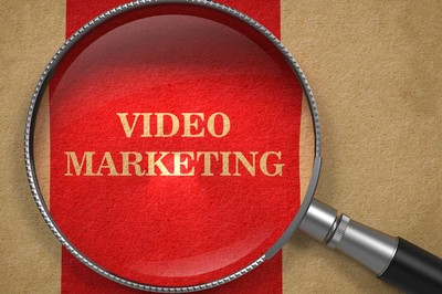 Video Marketing Concept. Magnifying Glass on Old Paper with Red Vertical Line Background.