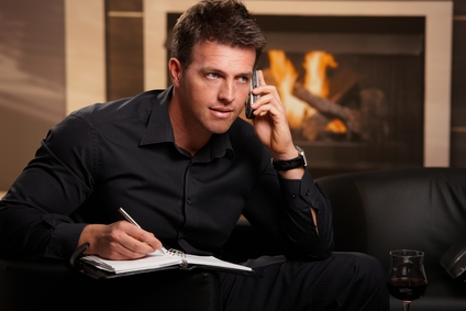 Businessman working at home sitting in front of fireplace, talking on mobile, making notes.