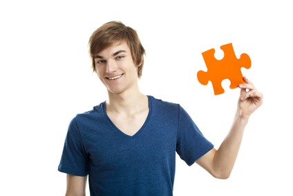 Young man holding a puzzle piece isolated on white background, soluton concept
