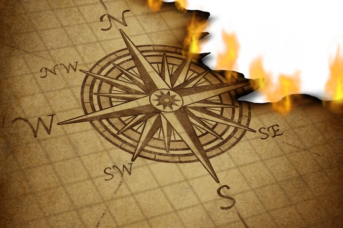 Losing direction and bad business planning and strategy with a compass rose navigation symbol on an old grunge parchment texture burning in flames as confused guidance.