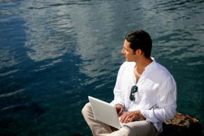 Man using his laptop by the water's edge