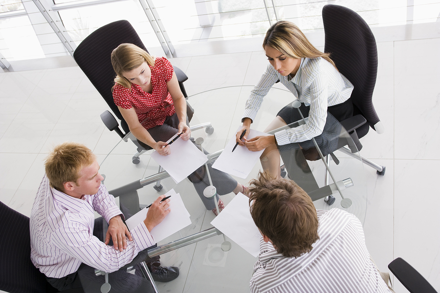 Group of business men and women sat round a table