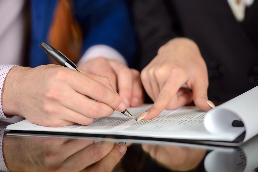 Businessman and woman hand signing contract paper ** Note: Shallow depth of field
