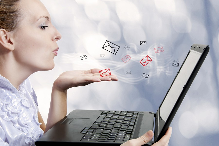 Concept - young attractive woman with laptop computer sending emails on forum chat or blog. Blogger