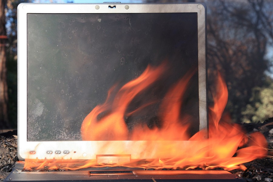 A genuine Lap Top Computer completely engulfed in flames of fire.  Computer damage due to a person typing so fast they burned up the internet or were writing something so HOT it literally caught fire