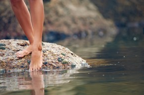 Woman on rock at beach dipping toes in water, having fun outdoor