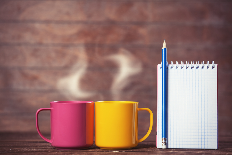 Two cups of coffee and notebook on wooden background.