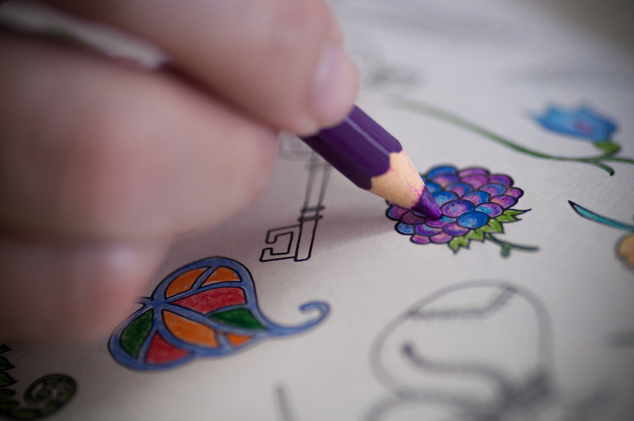 Detail image of adult person painting a coloring book. ** Note: Shallow depth of field