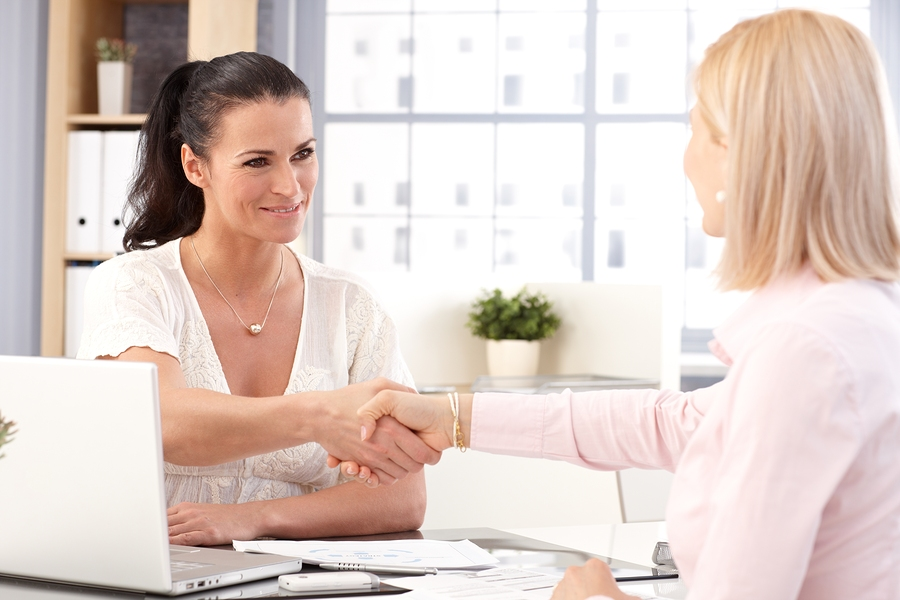 Happy casual brunette businesswoman working with laptop computer, shaking hands with client.