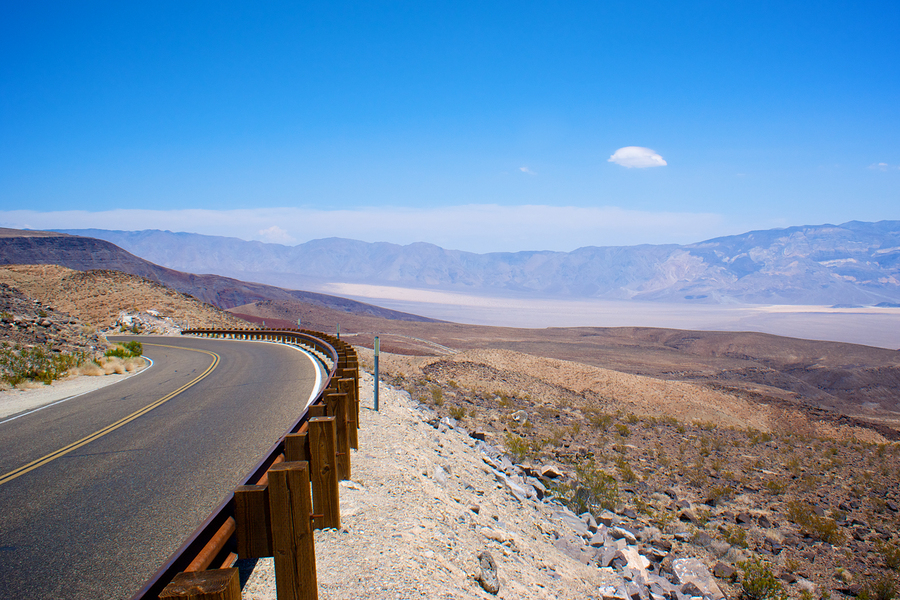 Winding asphalt road bends around a corner in the mountains over Death Valley National Park.