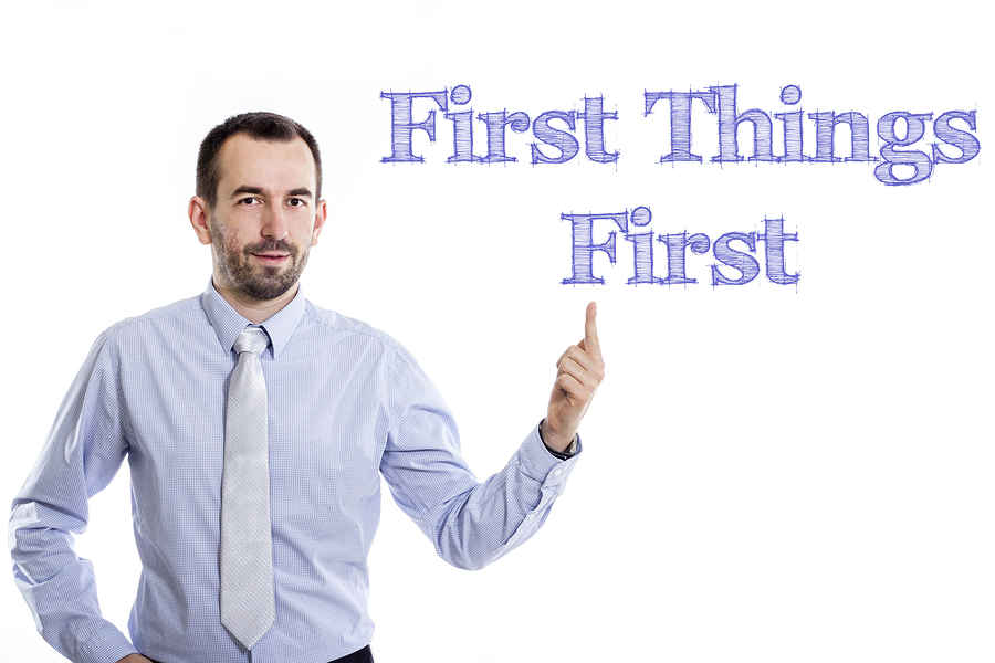 First Things First - Young businessman with small beard pointing up in blue shirt