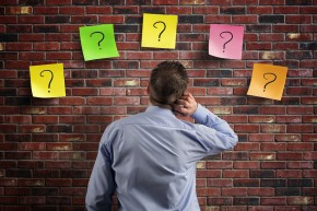 Businessman looking at a wall of questions