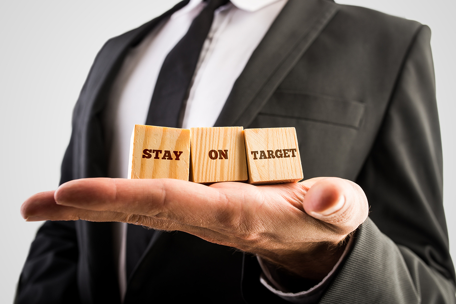 Businessman Holding Three Wooden Cubes With A Stay On Target Mes