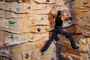 Active young woman on rock wall in sport centre.