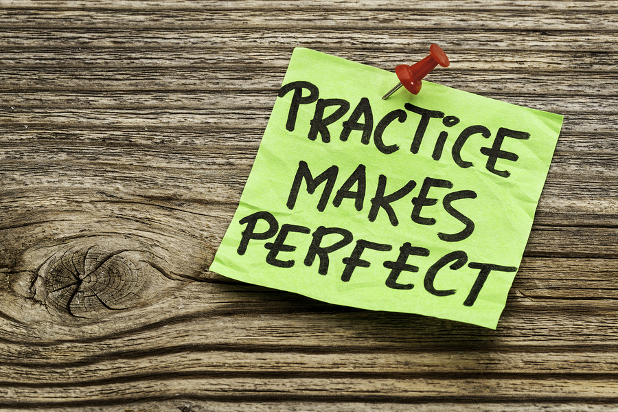 practice makes perfect - a motivational reminder on a green stoc