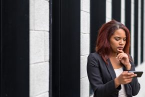 Businesswoman Reading On Mobile Phone