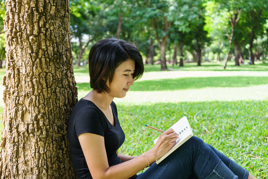 Asian Young Girl Write Letter Under The Tree
