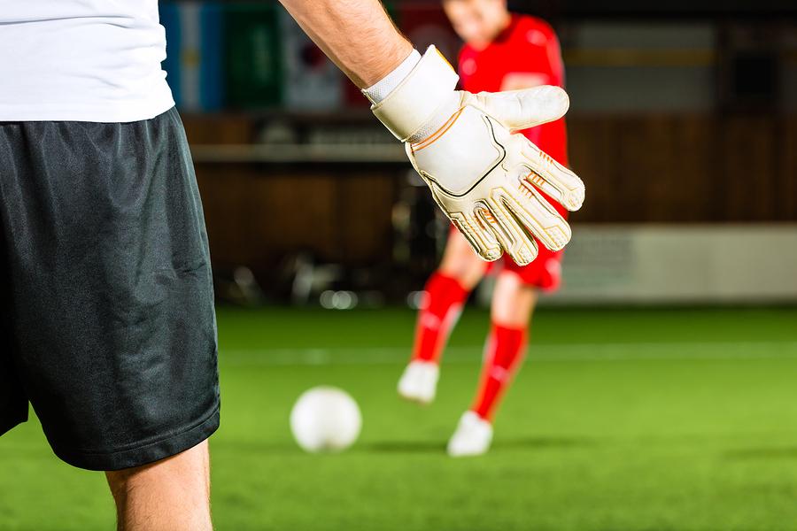 Man scoring a goal at indoor football or indoor soccer
