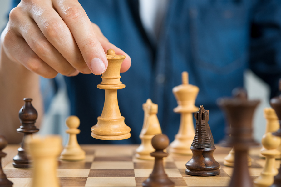 Close up of hand of man playing chess holding queen. Business ma