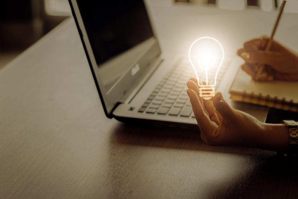 bright lightbulb by laptop - idea concept