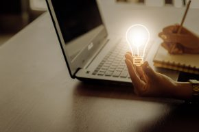 bright lightbulb by laptop - idea concept